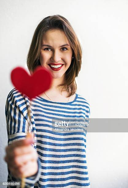 Beautiful young woman holding paper heart