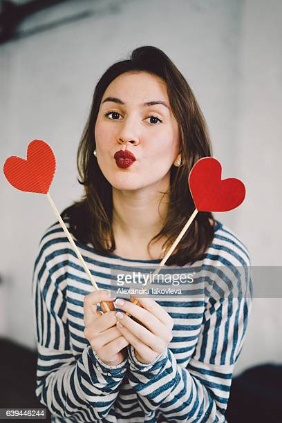 beautiful young woman holding paper hearts - heart month stock photos and pictures
