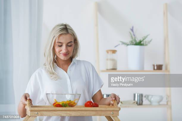 Beautiful young woman holding salad bowl and tomatoes in serving tray at kitchen