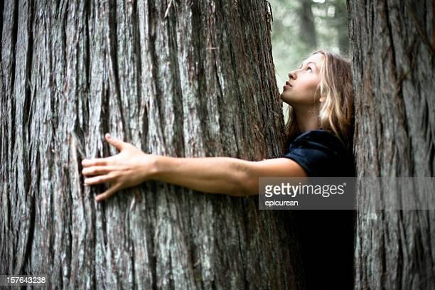 Schöne Junge Frau umarmen einen alten cedar tree