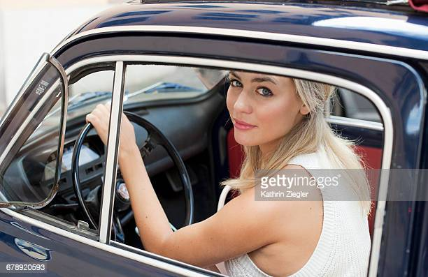 Beautiful young woman in a small vintage car