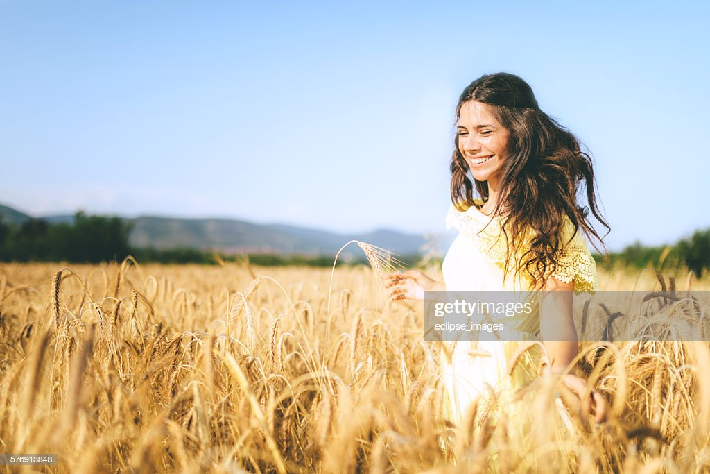 beautiful young woman in a wheat golden field : Stock-Foto