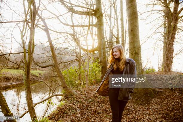 beautiful young woman in black walking by a river - theasis stock pictures, royalty-free photos & images