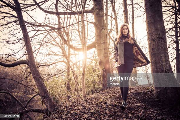 hermosa joven de negro caminando por un río - theasis fotografías e imágenes de stock