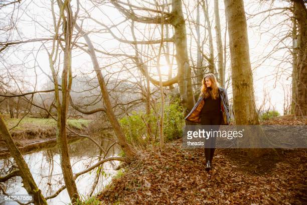 beautiful young woman in black walking by a river - pollock country park stock pictures, royalty-free photos & images