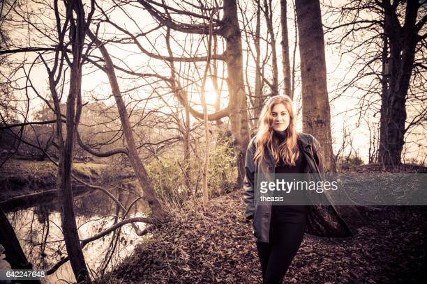 Beautiful young woman in black walking by a river
