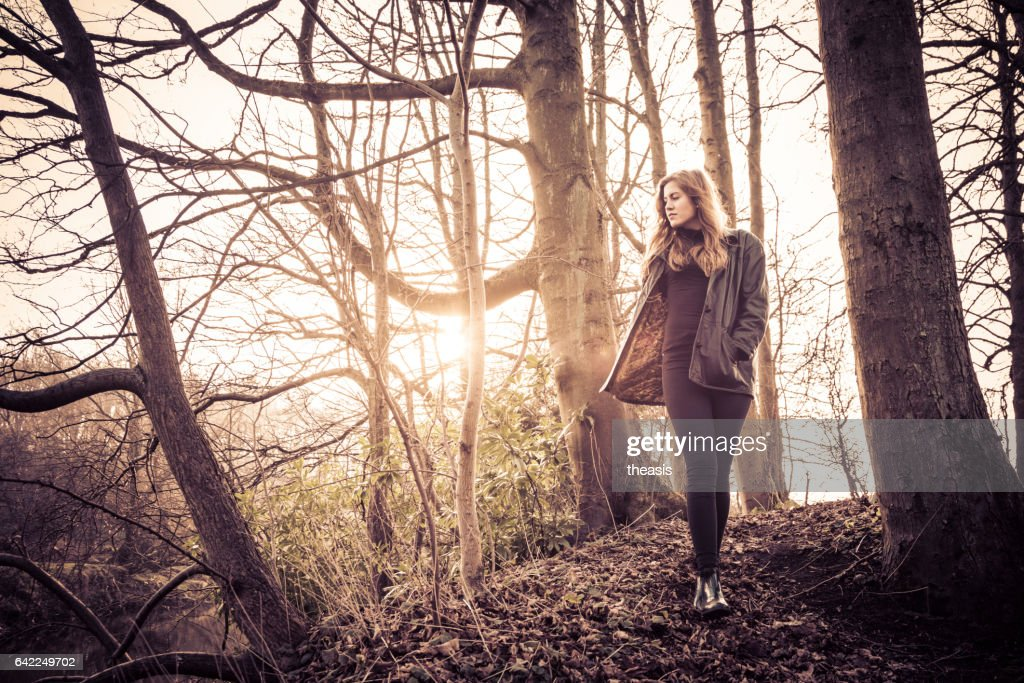 Beautiful young woman in black walking by a river : Stock Photo