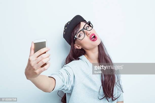 Beautiful young woman in contemporary outfit taking selfie