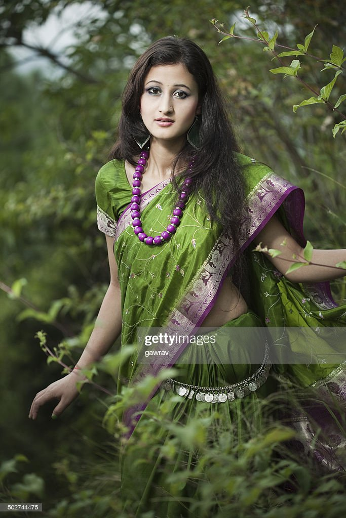 Beautiful young woman in green sari between nature. : Stock Photo