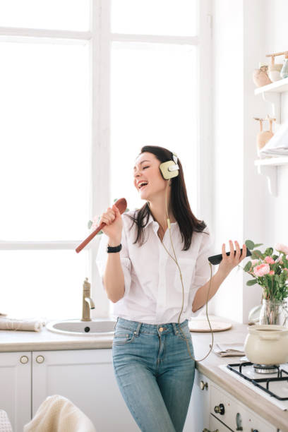 beautiful young woman in headphones cooking and dancing in kitchen. - singing stock pictures, royalty-free photos & images