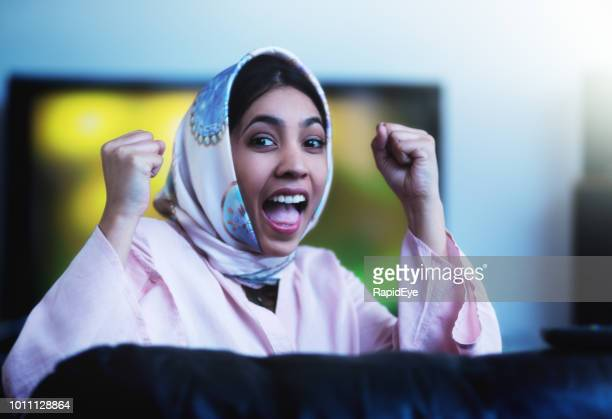 beautiful young woman in headscarf cheering with both fists clenched - muslim woman darkness stock photos and pictures