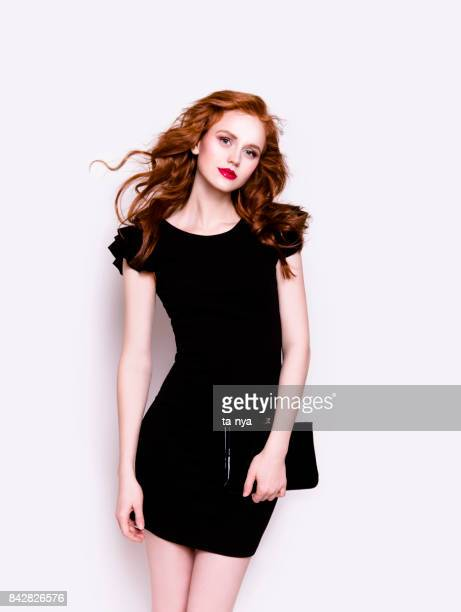 Beautiful young woman in luxury black cocktail dress holding clutch