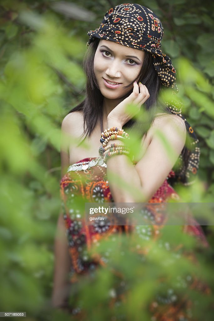 Beautiful young woman in nature behind foliage. : Stock Photo