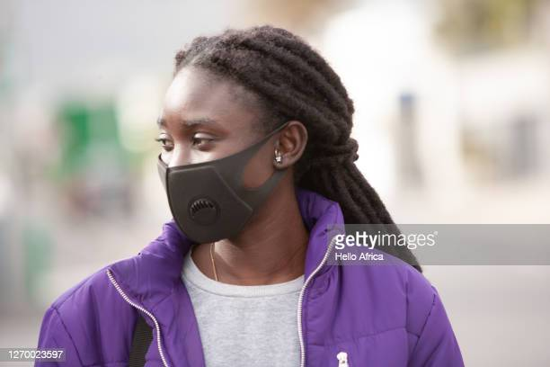 beautiful young woman in purple wearing a protective face mask - lilac fashin stock pictures, royalty-free photos & images