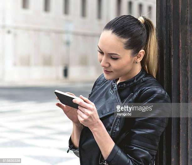 Hermosa mujer joven usando teléfono inteligente en la vida real