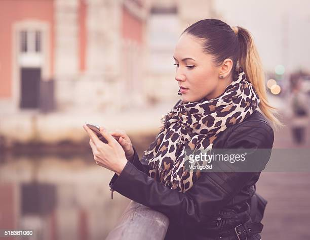 Beautiful young woman in real life using smartphone