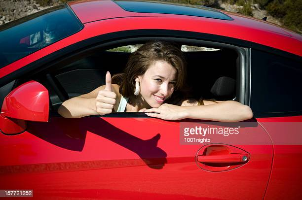 Beautiful young woman in red car