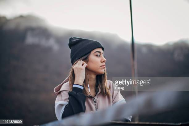 beautiful young woman in sports clothing is listening to music - woolly hat stock pictures, royalty-free photos & images
