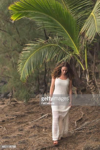 Beautiful young woman in sundress walks along rocky Hawaii coastline