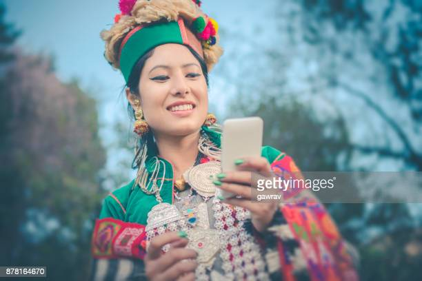 Beautiful young woman in traditional dress of Kinnaur holding smartphone.