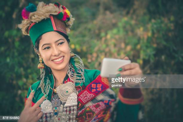 Beautiful young woman in traditional dress of Kinnaur taking selfie.