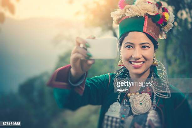 Beautiful young woman in traditional dress of Kinnaur taking selfie.