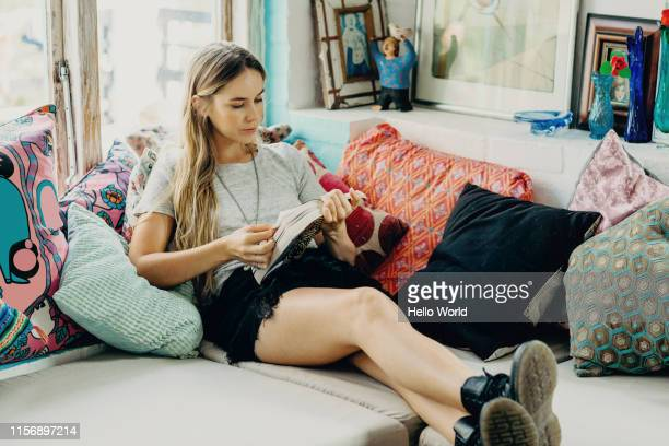 beautiful young woman intently reading on the couch - solitude stock pictures, royalty-free photos & images