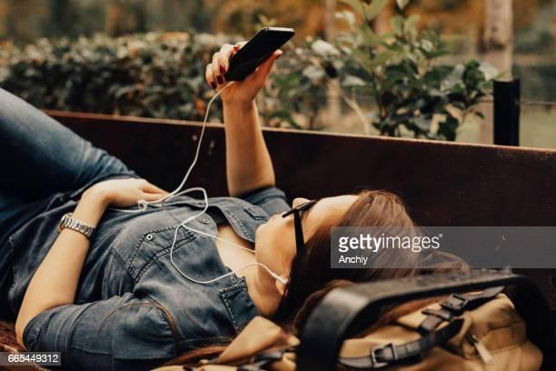 Bella joven es escuchar la música en su teléfono