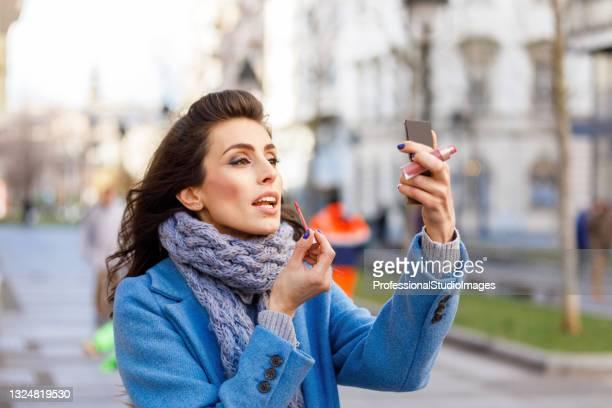 schöne junge frau steht auf der straße und trägt einen lippenstift auf. - frauen über 30 stock-fotos und bilder