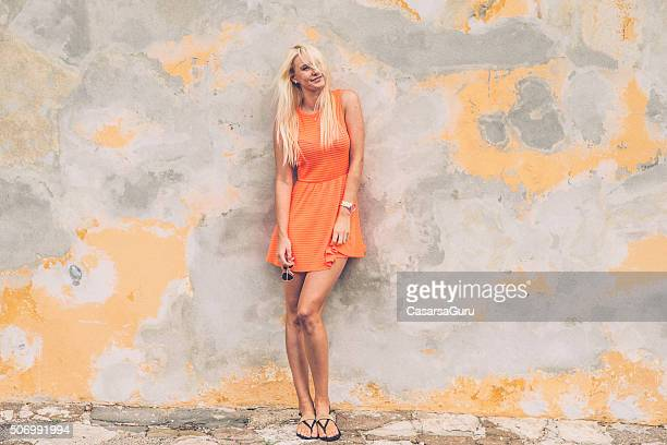 beautiful young woman leaning against wall, copy space - sundress stock pictures, royalty-free photos & images