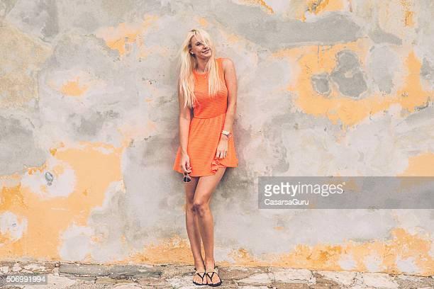 美しい若い女性の壁に壁、コピースペース - サンドレス ストックフォトと画像