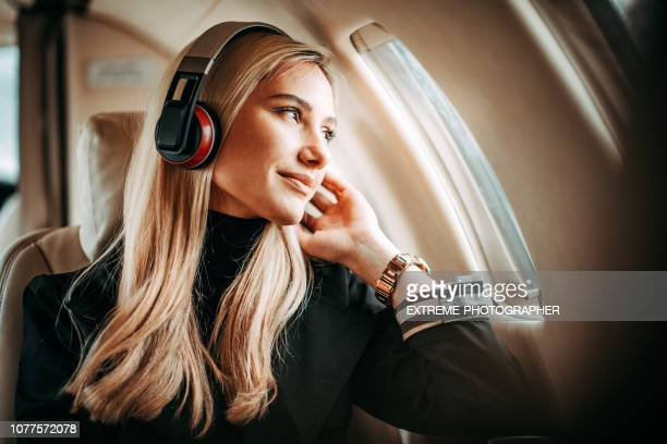 beautiful young woman listening to music through the headphones in a private jet - volare foto e immagini stock