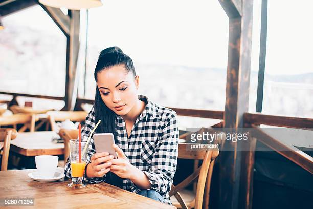 Beautiful young woman looking at her phone in the cafe