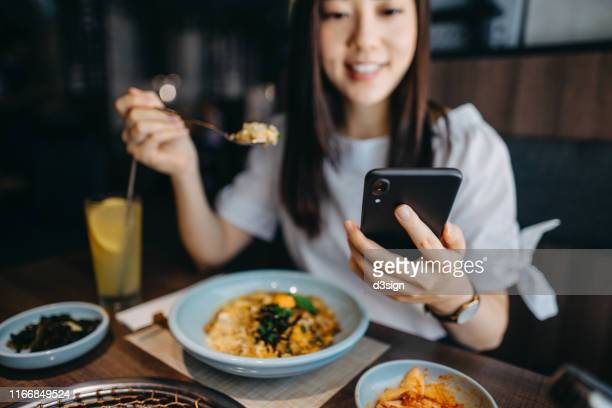 beautiful young woman looking at smartphone while having lunch in a restaurant - 昼食 ストックフォトと画像