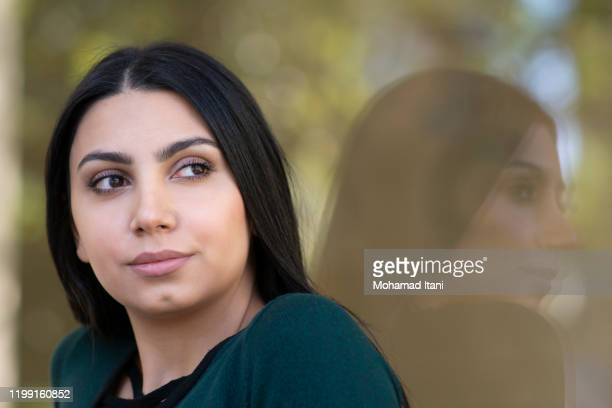 beautiful young woman looking away outdoors - black hair stock pictures, royalty-free photos & images