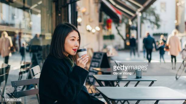 beautiful young woman looking away while drinking coffee sitting at sidewalk cafe - restaurant stock pictures, royalty-free photos & images