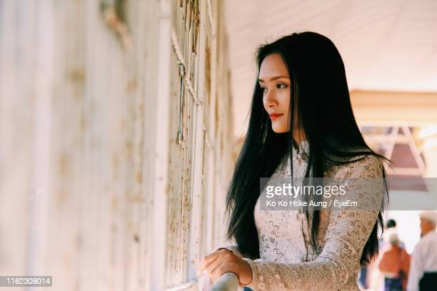 beautiful young woman looking away while standing by window - ko ko htike aung stock pictures, royalty-free photos & images