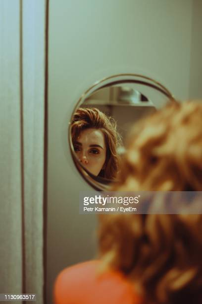 beautiful young woman looking in mirror at home - china: through the looking glass stock pictures, royalty-free photos & images