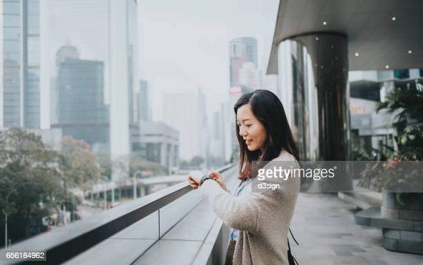 Beautiful young woman looking on her smart watch in office building
