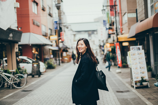Beautiful young woman looking over shoulder with smile whilst strolling in city - gettyimageskorea