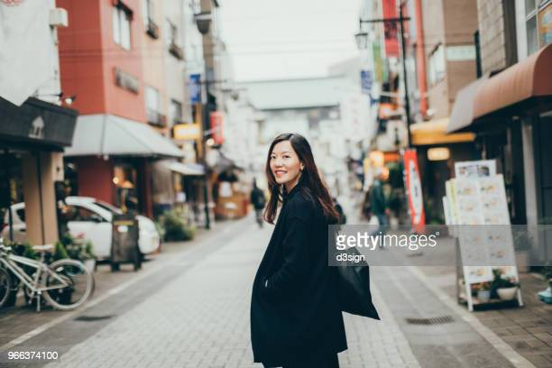 beautiful young woman looking over shoulder with smile whilst strolling in city - 肩ごしに見る ストックフォトと画像