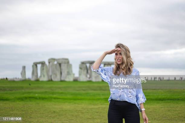 beautiful young woman looking under her hand standing next to stonehenge - religious equipment stock pictures, royalty-free photos & images