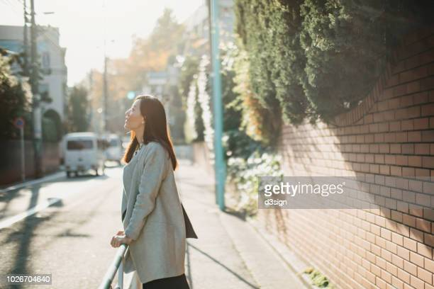Beautiful young woman looking up to sky enjoying the tranquility and warmth of sunlight in urban sidewalk
