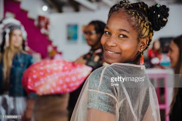 beautiful young woman looks at camera over shoulder with friends in background - cape town stock pictures, royalty-free photos & images
