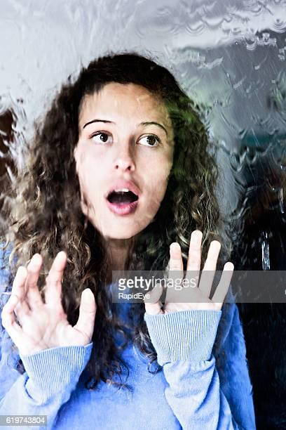 Beautiful young woman looks through rain-streaked window, surprised