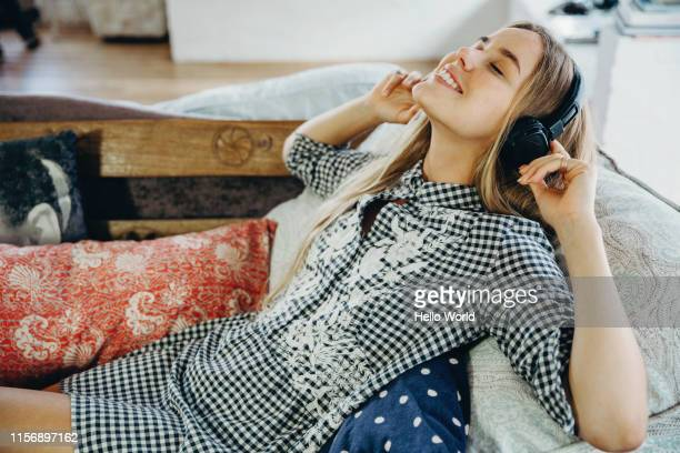 beautiful young woman loving listening to music on the couch - headphones stock pictures, royalty-free photos & images