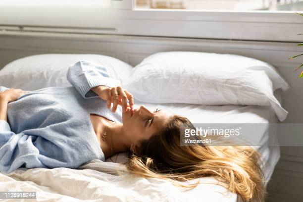 beautiful young woman lying in bed looking up - women touching herself in bed stock pictures, royalty-free photos & images