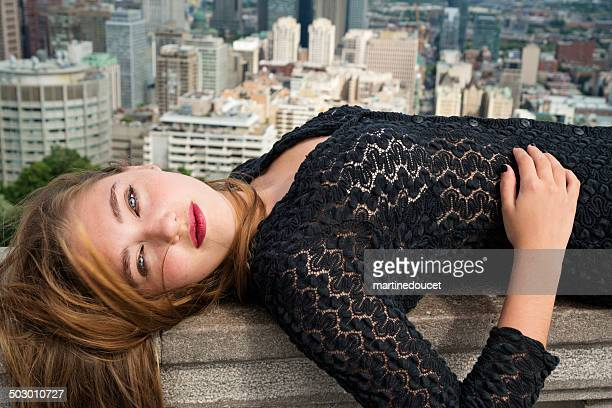 Beautiful young woman lying in front of cityscape.