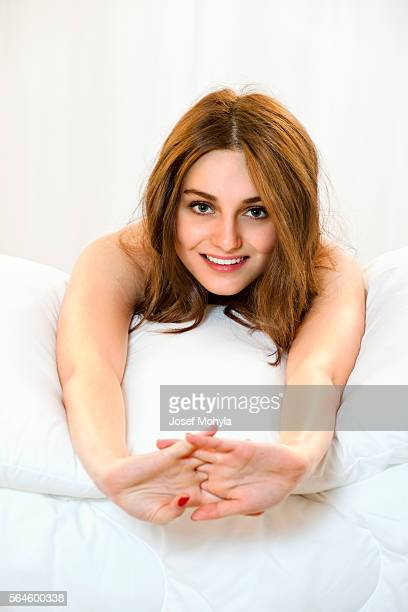 Beautiful young woman lying on front in bed and stretching