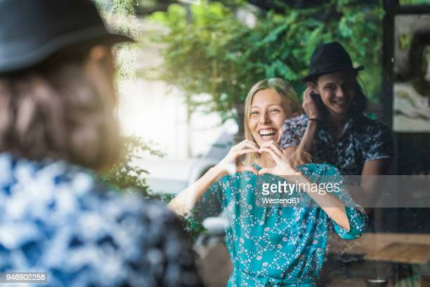beautiful young woman making a finger frame heart and smiling at her boyfriend through a window - gebaren stockfoto's en -beelden